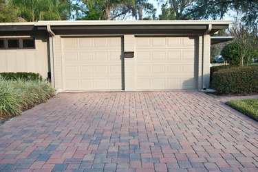 Beige Two Car Garage with Brick Driveway attached to Home