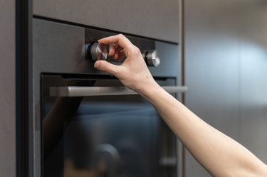 Side view photo of woman hand tuning program on control panel for built-in oven in black kitchen cabinet