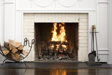 White brick fireplace with fire burning, stack of logs on rack, and fireplace tools