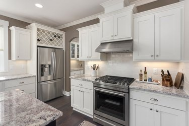 beautiful kitchen in new luxury home with island, stainless steel appliances, and hardwood floors.