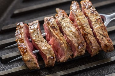 Slice of Grilled Steak with Seasoning  on a Fork and Cast Iron Grill