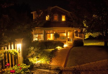 Seaside cottage with screened porch, brick walkway and a American flag, all illuminated at night