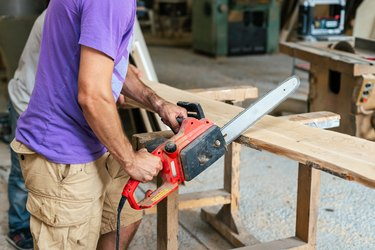 Manual wood concept. Profile side view cropped photo of cabinetmaker handyman tradesman holding chainsaw in hands sawing wood board make furniture in work shop or workroom