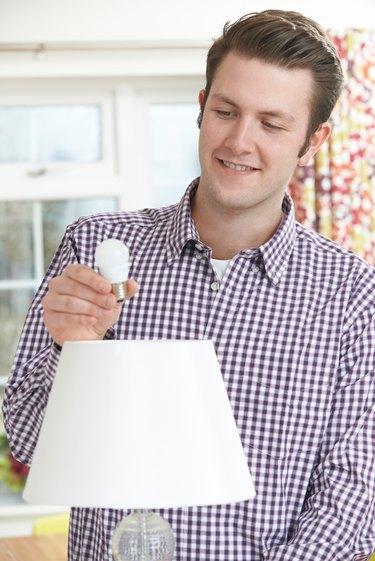 Man putting LED lightbulb into lamp.