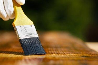 Paintbrush sliding over wooden surface.