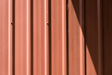Brown corrugated metal sheet with bolts.