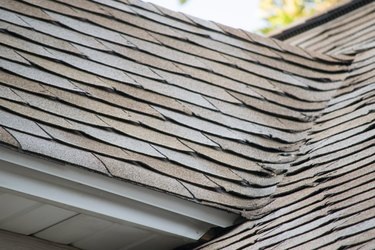 Damaged and old roofing shingles on a house.