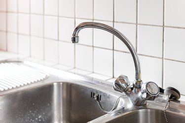 Old stainless steel faucet and kitchen room double sink closeup with two dials and tile backsplash in home or apartment
