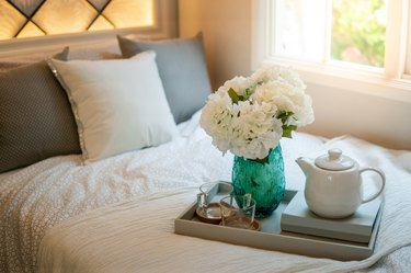 Bedroom decorative objects on the bed in cozy vintage bedroom. Flower vase, ceramic tea pot, glass cups and book. Home decoration concept