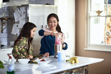 Woman using smoothie maker with daughter watching in kitchen