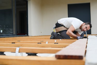handsome young man carpenter installing a wood floor outdoor terrace in new house construction site