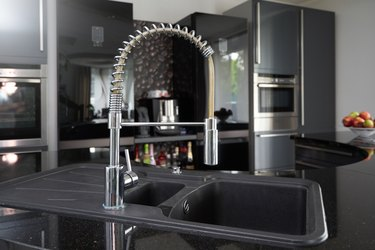 Black kitchen sink and chrome tap that can be pulled out for comfortable washing