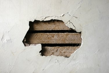 Hole in Plaster Wall - Exposed Wood Paneling