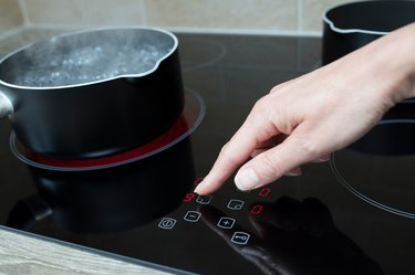 Close Up Of Woman Adjusting Temperature Of Halogen Hob In Kitchen