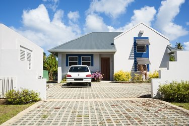 Car in a driveway at a white Caribbean style home