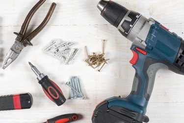 Acu drill screwdriver rachet and tools flat lay over wooden background