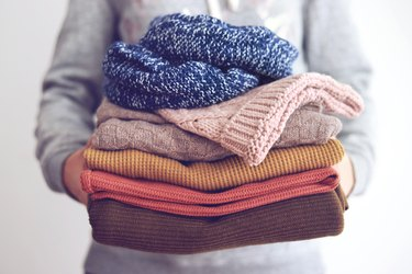 Midsection Of Woman Hand Holding Sweaters