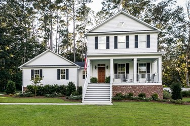 Front of new construction white siding farmhouse in the suburbs