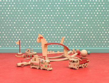 Wood and plastic vintage style playroom with cockhorse and toys on green and red background, 3d Rendering