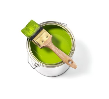 Green paint tin can with brush on top