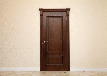 empty beige room interior with brown wooden door
