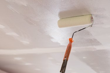 Workers are using paint roller on the ceiling