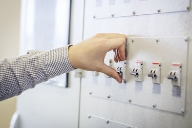 engineer switches on circuit breaker in electric switchboard close-up. Supply electricity concept. electrician's hand against electrical panel background.