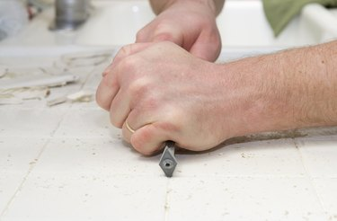 Male hand removing grout from kitchen tiles