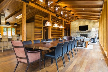 Wooden dining table with rawhide armchairs, black leather chairs and illuminated industrial style copper with frosted glass pendant lighting fixtures in dining area of great room with Ipe wood floor plus view of living room area with natural stone firepl
