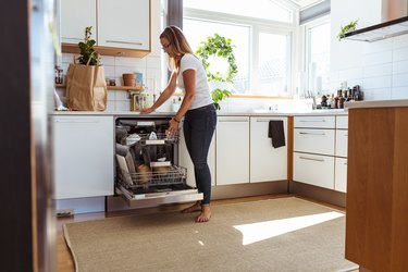 Full length of woman using dishwasher while standing in kitchen