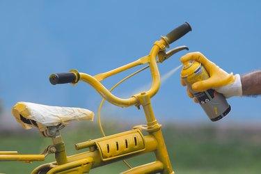 Photo of yellow bike painting with yellow glove