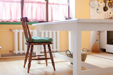 Kitchen scene with white table, wooden chair and green cushion. Cozy home with wisker basket on floor and heating battery under big window.
