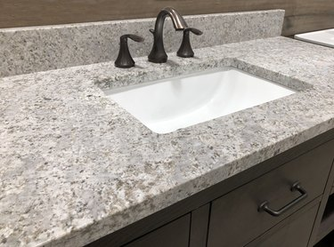 bathroom granite counter over wooden vanity cabinet and white rectangular sink with chrome faucet