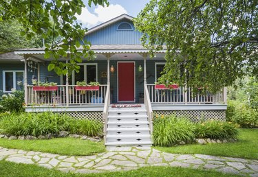 Country cottage style residential home facade with veranda in summer