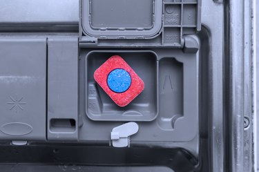 A tablet of a detergent for washing dishes in dishwashing machine container