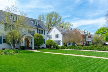 Wide green front lawns in traditional suburban residential neighborhood