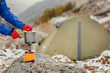 gas cartridge camping jet stove with modern titanium pot on it on a background of the tent during hiking