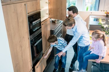 Scene in a kitchen showroom, family shopping for a new model