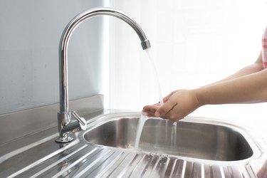 Washing hands at sink.
