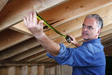 Man measuring distance between rafter beams of home addition.