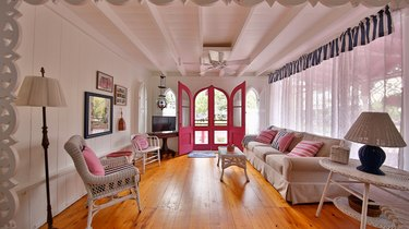 the pink house living room with wicker furniture and fabric couch