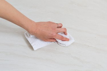 Hand with cleaning cloth wiping counter