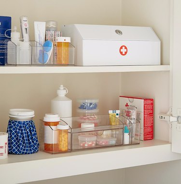 Medicine Cabinet Organization ideas in Medicine cabinet with first aid kit, clear organizers, pills.