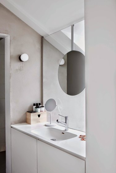 monochrome bathroom with deck-mounted facuet on white countertop