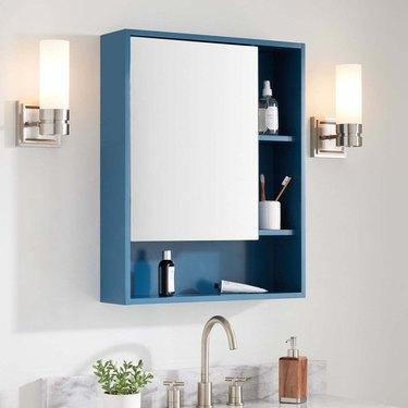 Medicine Cabinet Organization ideas in Blue medicine cabinet with open shelves, sconces, sink.