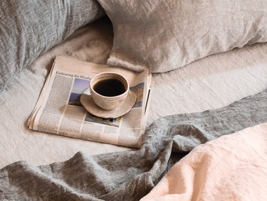 coyuchi bed seen from above with linen sheets and newspaper with mug of coffee