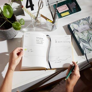 hands on open planner on desk