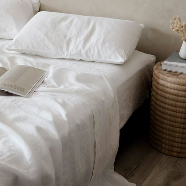 cultiver bed with white linen sheets
