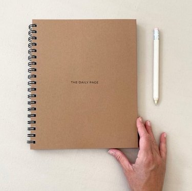 brown spiralbound planner with pencil and hand