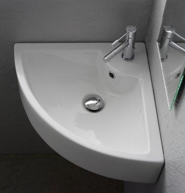 White ceramic corner bathroom sink with silver hardware in gray bathroom